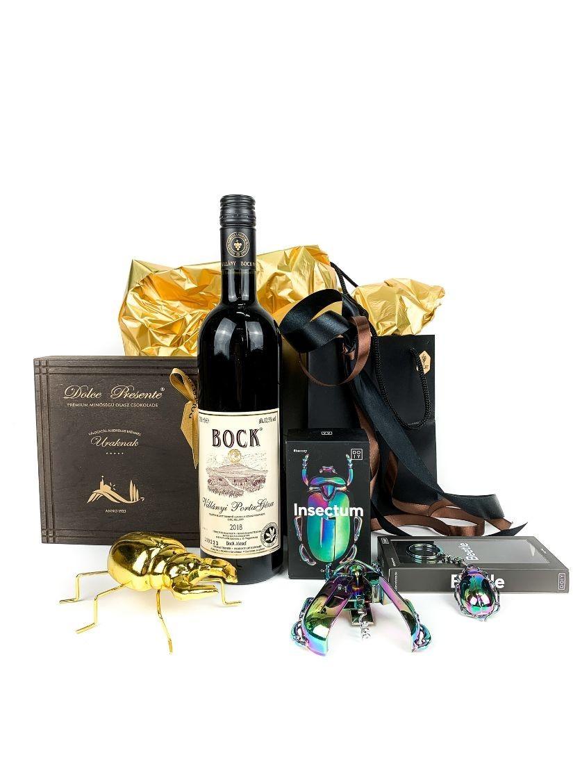 Egy üveg minőségi Bock vörösbor fekete tasakba, egy fa dobozos olasz csokoládé és bogár