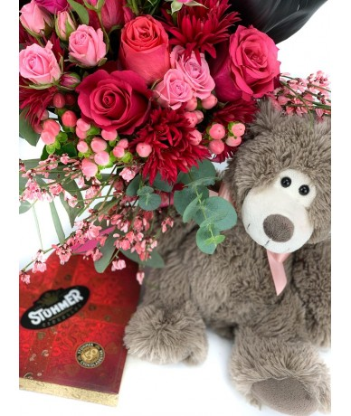 Teddy bear with a truly romantic bouquet of red-pink flowers, chocolate and teddy bear
