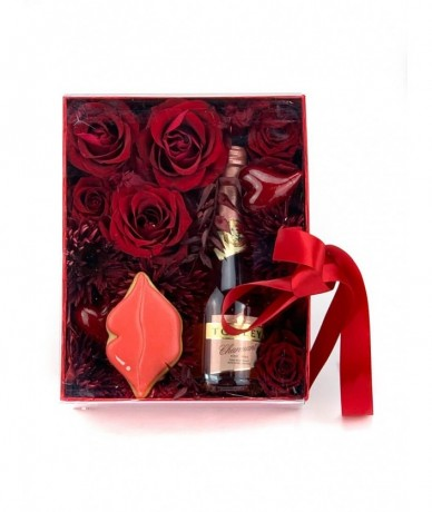 Enchanting gift package with red flowers, champagne and cake