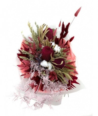 Egy csokornyi bordó-pink-pasztell szárított virág, papírzacskóba csomagolva