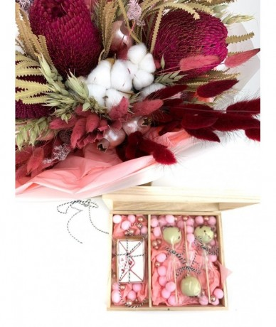 Dry pink-red pastel bouquet in a trendy paper bag with lollipop box