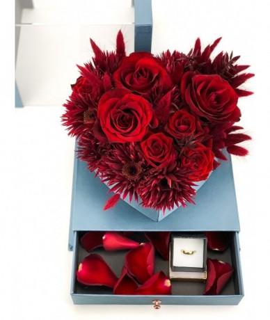 Virágdoboz vörös virágokból elegáns kék dobozban, szirmokkal teli fiókkal, szalaggal átkötve