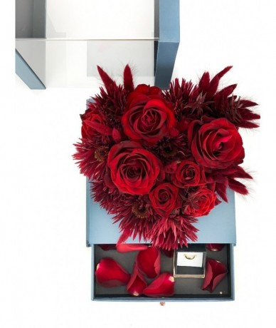 Red flowers in an elegant heart-shaped blue box with a drawer