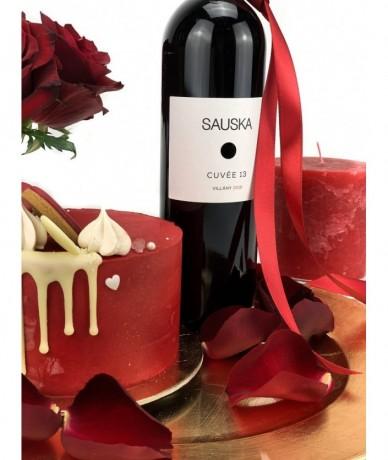 Arany tálcán kis rózsacsokor, egy üveg vörösbor, egy minitorta és egy gyertya szirmokkal
