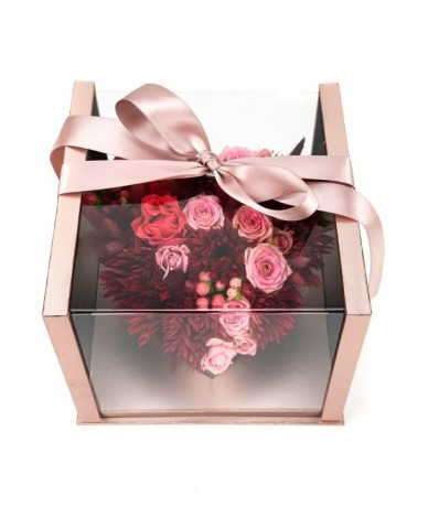Rose-coloured box with transparent lid and a ribbon, inside a heart formed by red and pink flower heads