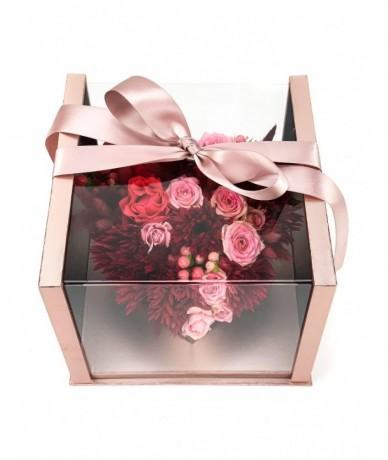 Rozé színű átlátszó fedelű dobozban romantikus oink-vörös virágok szív formában, szalaggal átkötve