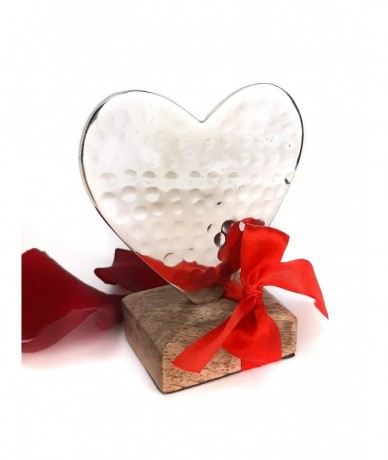 Palm-sized metal heart on a wooden base