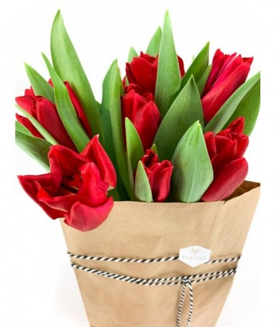 A paper bag packet of red tulips with a love muffin
