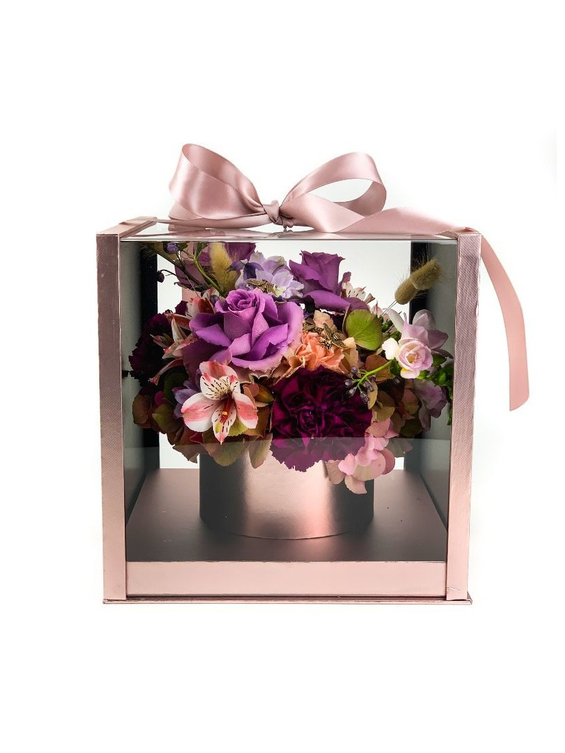 Luxurious rosé and transparent gift box with a small mixed bouquet