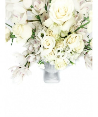 Countless white orchids and roses explode out of a pot
