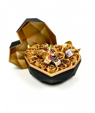 Golden roses in a golden-black metal box with chocolates
