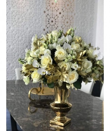 Orchids and roses in a majestic pairing with golden leaves