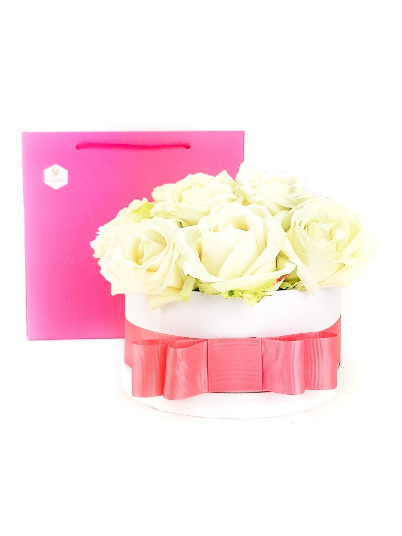 White roses in a white box with pink ribbon